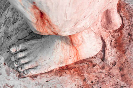 Extreme close-up of the feet of Jesus Christ bloodied. Top view. Shallow depth of field. Stock Photo