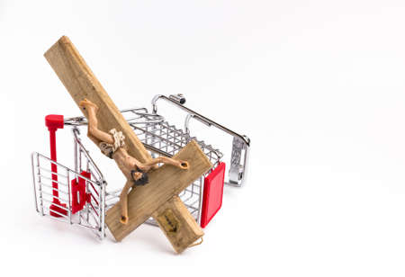 blasphemy: Shopping cart overturned with crucifix on the ground. Conceptual representation of commodification of religion, loss of faith, blasphemy.