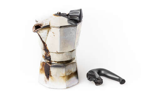 Vintage Moka pot forgotten on the fire. Burned with in molten plastic components. Stock Photo