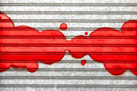 Red bubbles painted with spray paint on a roller shutter.