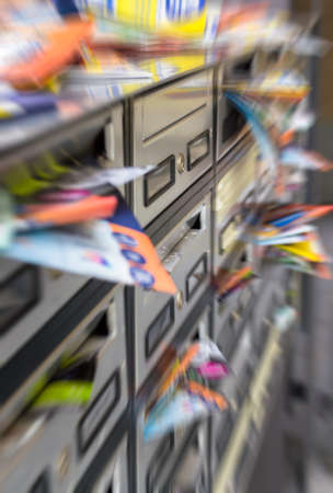 Mailboxes filled with paper flyers. Symbol for advertising, mail, marketing, spam. Defocused blurry background.