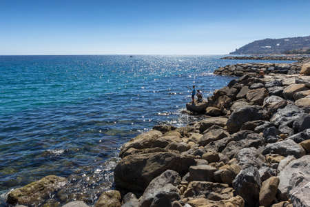 Amazing sea with blue summer wave and rocks. Summer sea background. Endless sea. Daylight sea. Turquoise sea. Sea foam and brown rocks. Sunny day sea view. Sea rock.