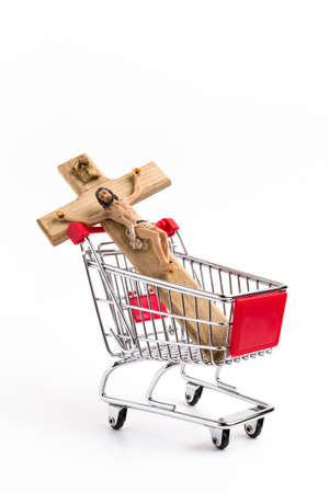blasphemy: Crucifix in shopping cart. Conceptual representation of commodification of religion, loss of faith, blasphemy.