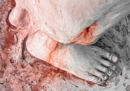 stigmata: Extreme close-up of the feet of Jesus Christ bloodied. Top view. Shallow depth of field. Stock Photo