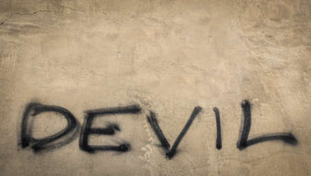 letterpress words: The word devil on grungy wall Stock Photo