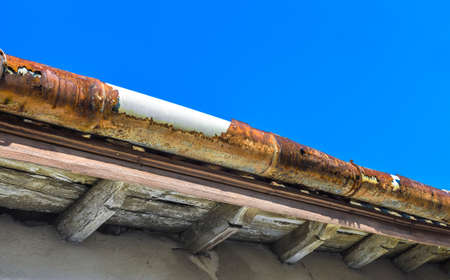 A broken gutter on the roof of a house Stock Photo
