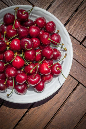 shallow: Ripe fresh rich cherries in the plate. Fruit background. Shallow DOF.
