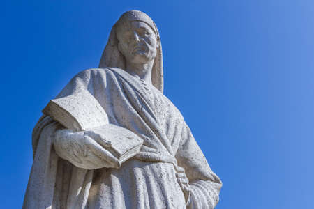 dante alighieri: Statue of Poet Dante Alighieri with blue sky in the background. The writer has a book in his hand. Stock Photo