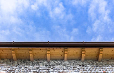 Low angle view of new house with wooden roof and gutter