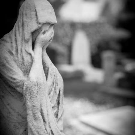 Old statue of a woman crying into her hands. Defocused blurry background. Stock Photo