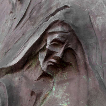 Detail of a mourning sculpture on a cemetery. (Religion, faith, suffering concept).