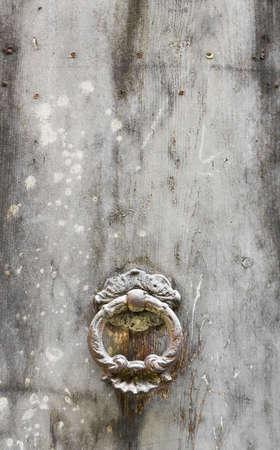 Ancient door knocker on white vintage background.