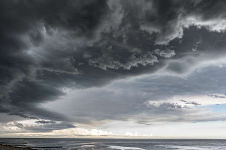 Landscape photo of a beach and dramatic thunderstorm clouds over the sea or the ocean Stock Photo