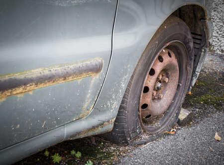 リムとフラットタイヤを備えたヴィンテージスクラップカーのクローズアップ 写真素材 - 92545975