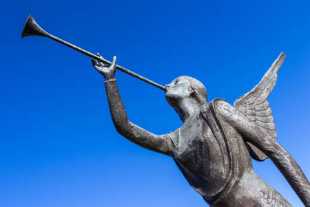 Statue of an angel playing a trumpet over blue sky 스톡 콘텐츠