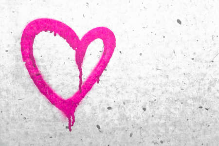 Pink heart symbol. Grungy wall background. Fall in love and Valentines day concept. Stock Photo