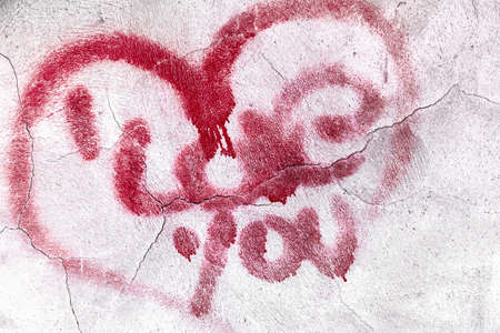 Red broken heart symbol with love message on textured cracked wall background 스톡 콘텐츠