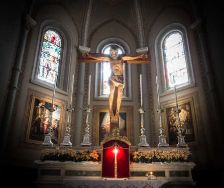 Classical Christian church in Italy. Wooden crucifix, candlesticks on the sides of it. Ideal for concepts and holidays.