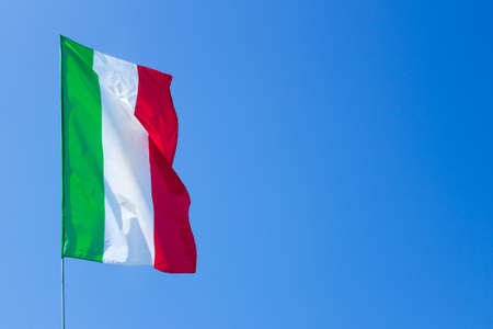 Waving Italian flag against blue sky