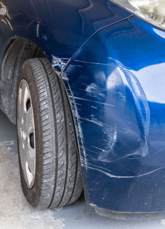 Blue scratched car with damaged paint in crash accident or parking lot
