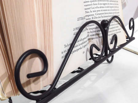 A lectern in a wrought iron keeps a book of stories open, ready to be read.