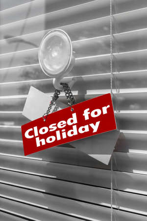 Sign saying Closed for holiday on a glass door with a white, closed venetian blind. It can be used for business concepts or backgrounds.