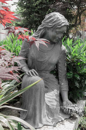 Statue at the cemetery. The representation of a girl who, bent over the grave, lays flowers.