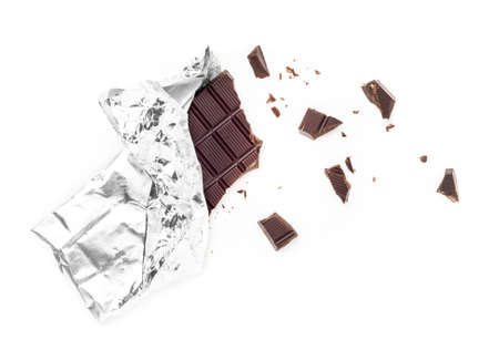 Chocolate Bar Tablet Wrapped in Aluminum Foil isolated over white Background. Some pieces are scattered around. Ideal for concepts.