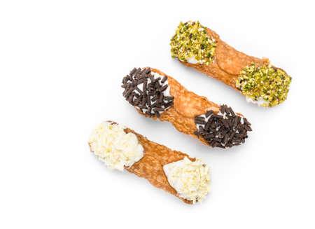 Three cannoli pastries. Traditional Sicilian dessert, filled with a rich ricotta cream enriched with pistachio grain, hazelnut grain and chocolate flakes. Archivio Fotografico