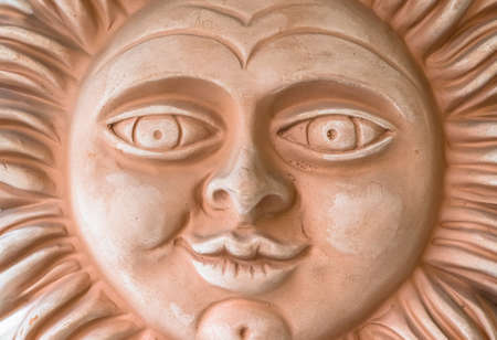 Smiling terracotta sun face. Closeup.