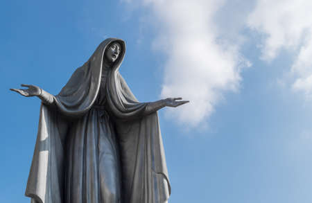 Statue of Virgin Mary in bronze, in a blue sky background with white clouds, with outstretched arms.