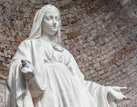Statue in stone of Virgin Mary. On background, red brick wall. Ideal for christmas and easter concepts and other.
