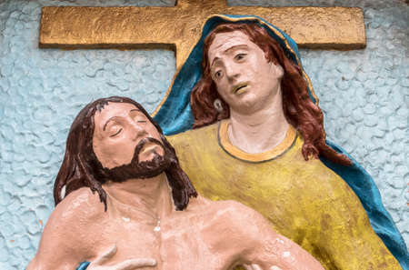 Religious stone statue in color representing The Pity of Michelangelo. Mary mother holding Jesus Christ on her lap after the Crucifixion.