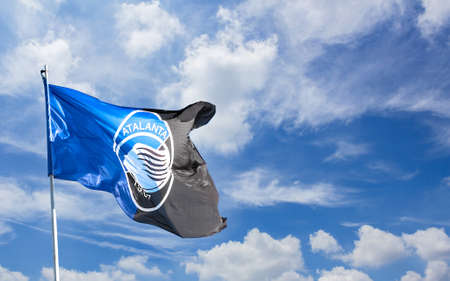 Atalanta flag waving against blue sky with white clouds. Space for text. Bergamo, ITALY - December 10, 2018