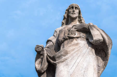 Stone statue of Sacred Heart of Jesus. Jesus Christ stone sculpture with heart on blue sky background. Ideal for easter concept and other.
