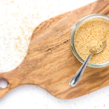Brown sugar in glass jar on wooden chopping board. Flat lay. Shallow dof.