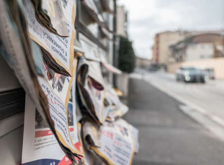 Many flyers in mailboxes, symbol for advertising, marketing, spam. Selective focus.