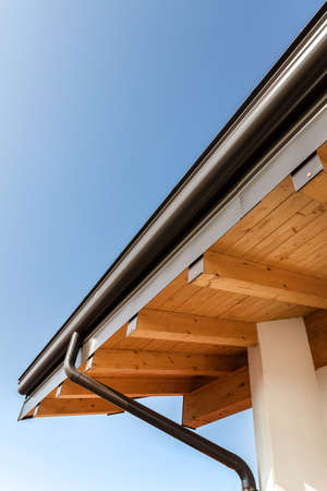 New wooden warm ecological house roof with steel gutter rain system. Professional construction and drainage pipes installation. Eco materials. 版權商用圖片