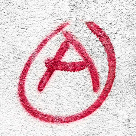 Symbol of Anarchy painted on a gray concrete wall. Ideal for concepts and backgrounds. Space for text.