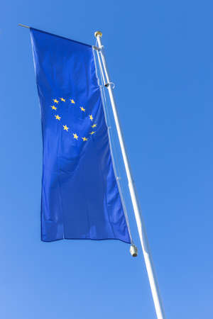 Flag of the European Union waving in the wind on flagpole against the blue sky.