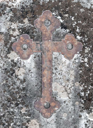 Ancient rusty cross on a old stone. Ideal for concepts and backgrounds.