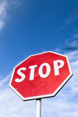 Stoppschild gegen blauen Himmel und weiße Wolken. Untersicht. Platz für Text. Standard-Bild