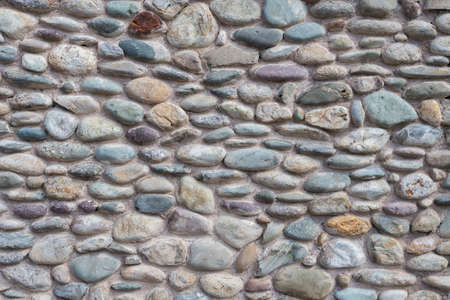 Wall with colorful cemented pebbles. It can be used as background.
