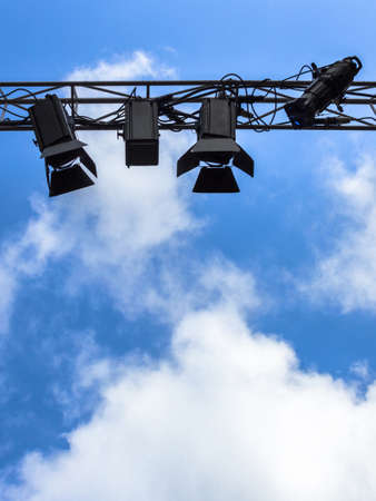 Spotlights for outdoor stage on the metal construction against a blue sky and clouds. Space for text. Reklamní fotografie