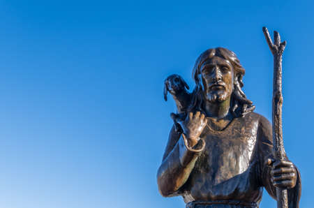 Ancient bronze statue of Jesus Christ the Good Shepherd with the lost sheep on his shoulders, isolated on a blue sky background. Space for text.