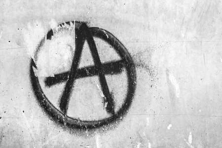 Symbol of anarchy painted on the peeling old wall. Ideal for textures, backgrounds and concepts.Space for text.