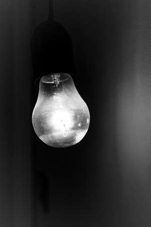 Old vintage light bulb glowing in the dark. Ideal for concepts.