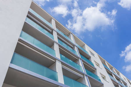 Modern new apartment with concrete exterior walls and large glass balconies in Italy.