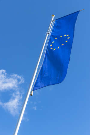 Flag of the European Union waving in the wind on flagpole against the blue sky with white cloud.