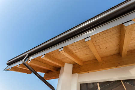 New wooden warm ecological house roof with steel gutter rain system. Professional construction and drainage pipes installation. Eco materials.